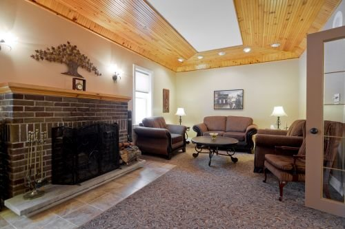 A photo of an interior planning room at Pilon Family Funeral Home showcasing a fireplace, comfortable couch, and seating.