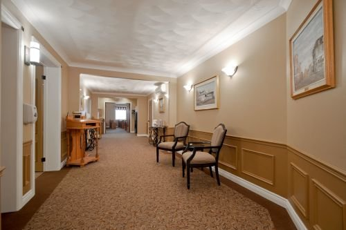 An interior hallway photo of Pilon Family Funeral Home showing comfortable seating and decorative hangings.
